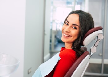 woman with veneers smiling in dental chair
